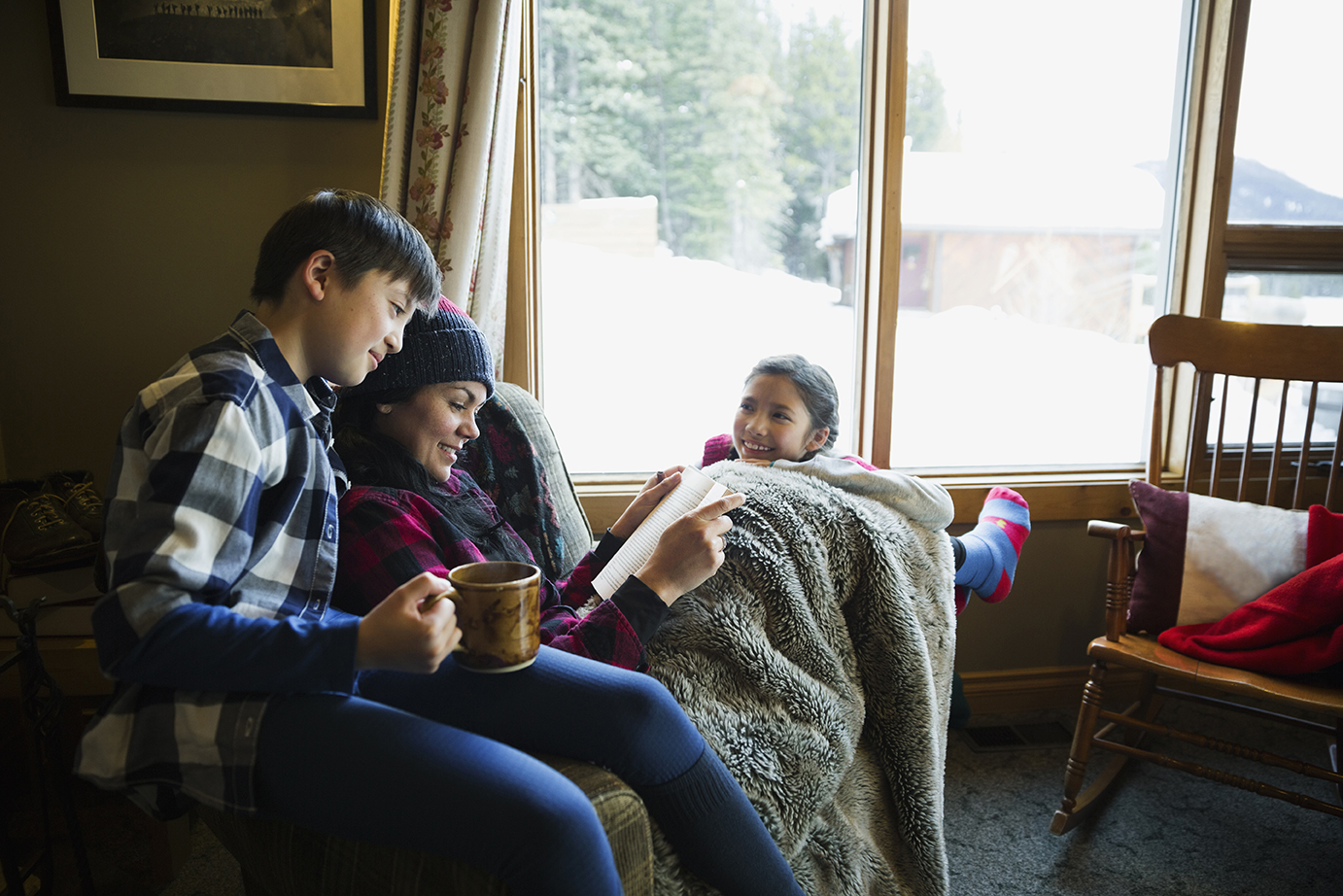 Family reading and relaxing in lodge living room
