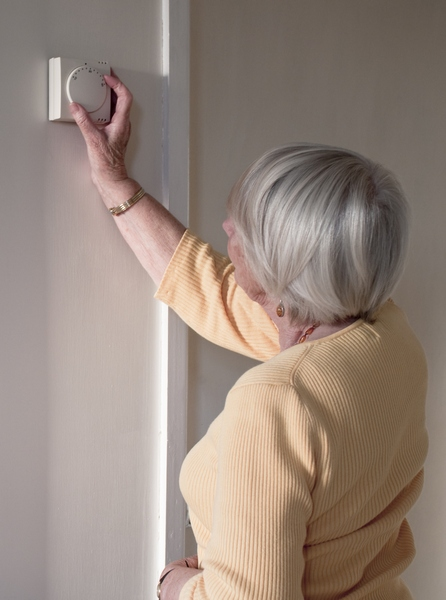 Elderly Lady Adjusting The Central Heating Thermostat